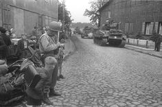 A US column of Sherman tanks advances through a suburb of Berlin, April 1945. A military policeman is taking notes. A schoolchild, carrying his backpack, is also watching. His haircut is typical German military. Other German civilians are also watching.