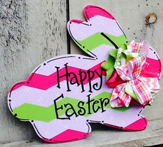 This fun decorative bunny door hanger is the perfect accent for any room or door to celebrate Easter and the Spring Season The design is a combo of classic chevron and small dots. Colors are a combo of pinks , lavenders and mint green which is painted with high quality acrylics and sealed for protection. The bow is multi patterned and fabrics. Combinations might vary due to availability. Any saying or monogram can be added just put into the notes all specifications. Colors and patterns ca...