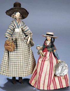 Two Small Grodnertal Wooden Dolls in Original Costumes. Petite dolls wearing their original costumes,one carrying sewing basket and the other carrying a tiny Grodnertal doll.