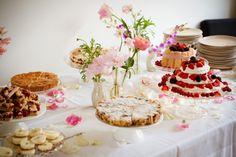 Taartentafel met taarten en bloemdecoratie in vaasjes