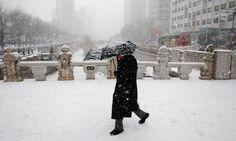 นักธุรกิจในเกาหลีใต้ เดินทางกลางหิมะตกหนัก ในย่านใจกลางกรุงโซล
