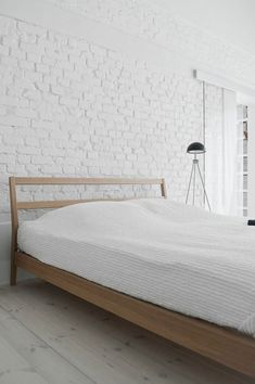 Bedroom with white brick wall and pine floor. Adaptation of a forge by Loft Szczecin. Photo by Karolina Bąk.