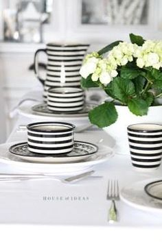 Stylish, black and white striped dishes and coffee cups.