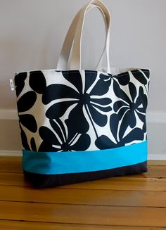 This EXTRA large beach bag is perfect for weekend trips, beach outings, vacation and so much more!     Exterior is a canvas black and cream floral print. This is an indoor/outdoor fabric, so very easy to clean. A turquoise accent stripe adds a punch of color. Bottom fabric is a black canvas. The interior is a natural colored canvas with an interior zip pocket.