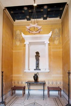 The hallway of Hermes opens out onto the apartments on the first floor of the Villa and corresponds to the Amphityros on the ground floor.  The terracotta centre light that lights up the room gives it a soft and intimate glow. This is the part of the Villa reserved for the apartments of Monsieur and Madame Reinach and guest bedrooms.    A niche, flanked by two elegant ionic columns, houses the bronze reproduction of a Hermes dedicated to Dionysus. The symbol of fertility, this statue was…
