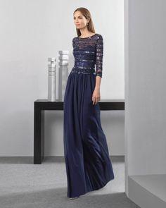 Vestido largo ligero con cuerpo de pedrería y falda de georgette y manga francesa, en color marino y plata.
