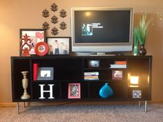 DIY bookshelf transformation. This was an ugly built in vertical bookshelf in our old house. When we moved I needed a horizontal surface and TV stand so created different sizes cubbies, turned the shelf horizontal, added legs from IKEA and painted. We love this piece!