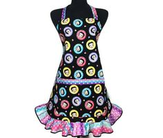 """This retro inspired kitchen apron is cut from a custom pattern and features an all over print of cartoon icon Betty Boop in multicolored circles on a black background filled with hearts and stars. The hostess style flounce ruffle, pockets and ties are all trimmed in a matching pastel rainbow and polka dot print. The fully adjustable """"D"""" ring neck and long waist ties make this a """"one size fits most"""" item. Bring a splash of color and style into your kitchen or cooking class today…"""