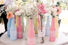 Idée déco DIY : des bouteilles de bière, de la peinture de différentes couleurs et un peu de dentelle -> bien nettoyer les bouteilles, les essuyer correctement avant de les recouvrir de peinture. Une fois les bouteilles bien sèches les entourer de dentelle !