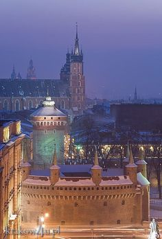 Widok na Barbakan, Bramę Floriańską i kościół Mariacki zimą: