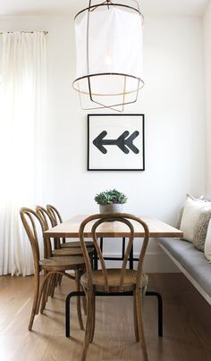 On the other side of the room, we couldn't help but fall for this breakfast nook. With wooden bentwood chairs, statement lighting, a fun print, and a cozy bench, you couldn't ask for a better place to start your morning.