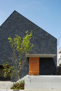 A pointy shingle-clad roof extends over this residence and garden by Suppose Design Office
