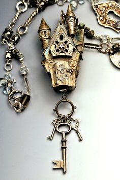Necklace | Christi Anderson. 'Fairy Queen of Keys Castle' Hand built from PMC+ this castle has windows, turrets and an opening door! Tiny rubies are set in the window panes. The entire piece is strung with hand built pmc hollow locks, keys and great assortment of gemstones