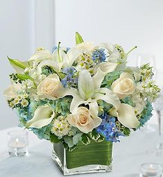 Blue and White Centerpiece Package Timeless beauty and elegant style are married in this centerpiece of white roses, white mini calla lilies, blue delphinium and more, in a modern glass cube vase.