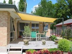 Instead of a pergola or umbrella - do a sailcloth over the patio. Do different colors on the main and secondary patio.