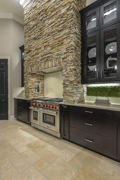 Stacked stone is used to create a stunning rustic range hood above the professional oven and stove. Neutral stone tile grounds the kitchen, while sleek black cabinets are paired with soft gray countertops.