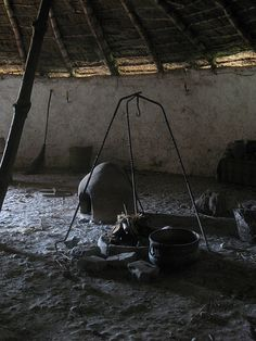 Iron Age Round House Interior... showing the cooking hearth with a tripod for suspending a cauldron and a bread oven.... Chiltern Open Air Museum, Chalfont, Buckinghamshire, England.