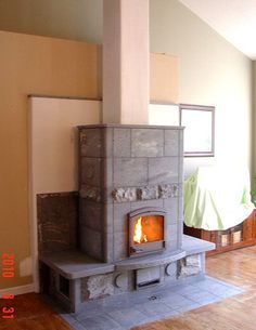 Masonry Heater Assoc pic. Design w/ benches on either side, central chimney.
