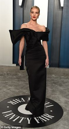 Glamorous: Rosie Huntington-Whiteley sported a black satin dress with an over-emphasized s...