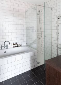 Bathroom, White Subway Tile With Black Tile Floors Is Complemented By A Wood Vanity And Simple Bathtub