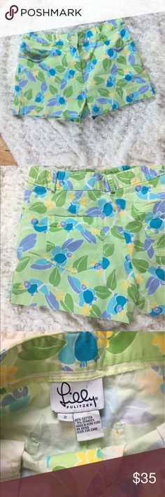 """Lilly Pulitzer Shorts Green Lilly Pulitzer shorts with flowers and tropical birds on them. Size 2. Waist 26"""", Hip 32, Inseam 2 1/4. Small area with loose stitching on back pocket shown in the last picture. Offers welcome. Lilly Pulitzer Shorts"""