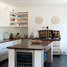 Discover kitchen design ideas on HOUSE - design, food and travel by House & Garden. In this modern country kitchen a wine fridge is built in to the island, while the fridge is inside a bookshelf.