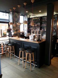 Réalisation du comptoir de bar en chêne massif, peint en noir satiné, de l'estrade et d'étagères diverses.