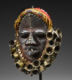 Africa | Mask from the We people of Liberia and Ivory Coast | Wood, fiber, bells, brass, shells, teeth and pigment | ca. 1970
