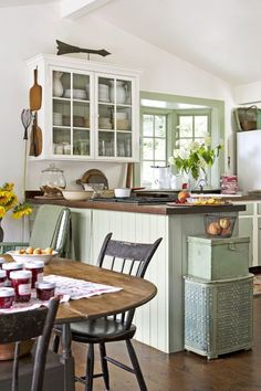 The owners of this Connecticut farmhouse borrowed from the verdant outdoors when creating the palette for the kitchen, hand-mixing the green paint used on the trim, work island, and some cabinet doors. Old chestnut boards reclaimed from the attic pave the room's floor.