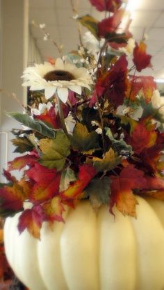 If you'd like an alternative from jolly jack-o-lanterns, this pretty floral arrangement, with white sunflowers and autumn leaves in a white pumpkin, would be a pretty Halloween centerpiece.