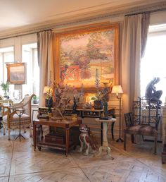Howard Slatkin NYC home:   In the living room an Impressionist painting of a view of Vernonnet with the Seine in the background hangs above a table filled with Chinese porcelain and tole flowering plants.