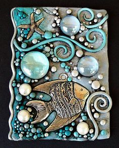 """I've made this ACEO from Polymer clay in blue and white and added a silver metal fish and starfish, pearls and glass gems. It was 'antiqued' with acrylic paint and then touched with pearl blue and silver metallic paint. A shimmery underwater scene! The glass gems remind me a liquid droplets and the tiny silver bits of clay sparkle like bubbles. It measures 2.5"""" x 3.5"""" which is the required size for an ACEO. ACEO stands for 'Artist Cards Editions and Originals' and can be made of any…"""