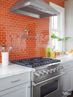 Instead of hanging upper cabinets, these homeowners refreshed their kitchen's outlook with glossy, light-reflective orange subway tiles running from the countertops to the ceiling. Each row of tiles is offset from adjacent rows to create a brick or running bond pattern, which brings a sense of movement to expansive tile installations.