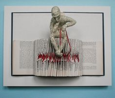 Clay sculpture and a cut book mounted on a wooden panel. Daniel Lai
