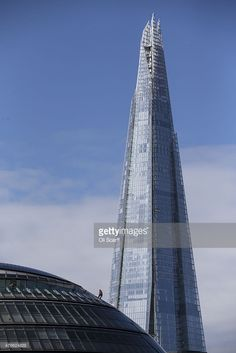 A construction worker abseils down the outside of City Hall in front of The Shard skyscraper on March 4, 2014 in London, England.