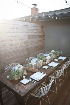 Rustic outdoor dining with a long wood table, white mesh metal chairs Outdoor Dinning Table, Rustic Table, Wooden Tables, Outdoor Living, Outdoor Decor, Outdoor Patios, Outdoor Spaces, Outdoor Seating, Rustic Patio