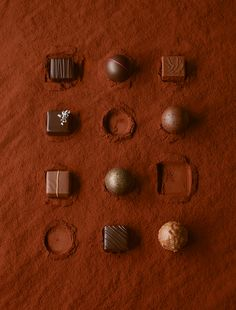 Luxury chocolates on a red cocoa powder background.