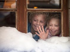 Brother and sister look out of their ski lodge window. The little girl's hand is against the window.