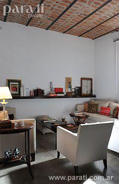 Los techos altos, las aberturas de pinotea, los espacios más que generosos... hacia ellos se enfocó el arquitecto Alberto Pedro Fassio a la hora de encarar el reciclaje de esta casa. El pequeño living da una prueba de ello. Al amparo de un cielorraso de bovedilla y perfiles de hierro totalmente recuperado, se disponen dos sofás con fundas de lino (Fradusco), un par de sillones con apoyabrazos (Bacano) y tres mesas de apoyo en madera lustrada: una tipo puente, otra auxiliar con patas tijera y…