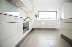 Classic warm white high gloss German kitchen and used Corian worktops to seamlessly compliment the minimalist design. #kitchen #design #white #gloss #minimalist
