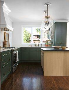 Beautiful Kitchen design by Ashley Montgomery Design.  I love the green kitchen cabinets and oversized pendant lights. #kitchen #greencabinets #darkwoodflooring