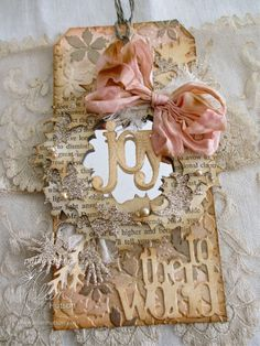 From Ellen Hutson.  Decorated collage tag with mirror plastic behind wreath.