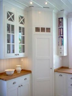 Corner pantry in White, scandinavian kitchen. I love the narrow shelves for books to the right!