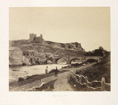 An albumen print photograph of Richmond Castle, North Yorkshire, taken by Roger Fenton in about 1854. Two men stand talking on the path beside the River Swale, in front of Green Bridge, built by John Carr (1723–1807) in 1788-1789. Fenton often placed people in his landscape and architectural photographs, providing a sense of scale and narrative.