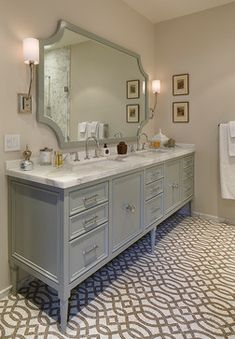 I love the blue/gray color of the vanity coupled with the chrome hardware and marble countertop. The uniqueness of the mirror design is also great. - Design courtesy of Tineke Triggs