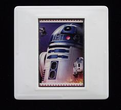 In 2018 the Royal Mail released a set of special stamps featuring some of the favourite droids, aliens and creatures of the Star Wars films. This 1st class stamp design shows R2-D2, a robot character who appears in nine out of the ten Star Wars films. The unused stamp is encased in a vintage slide mount, with glass, making this a unique piece of jewellery. Robots Characters, Star Wars Film, R2 D2, Royal Mail, Design Show, Postage Stamps, Aliens, Badges, Class Ring