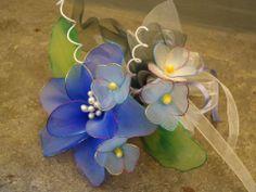 Bomboniera con giglio, piccoli fiori e trifogli, realizzata a mano con filanca setata, tulle e organza, possibilità di personalizzazione.