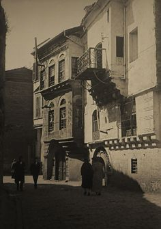 Achille Samandij  The main street of Phanar. Two men wearing suits and fezes walk past two Greek bourgeois ladies who are ambling down the street, arm in arm, wearing the latest fashions. (about 1920). On the left Byzantine sea wall.