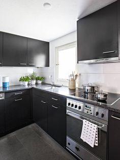 Tummanharmaat, melkein mustat keittiönkaapit on teetetty puusepällä mittojen mukaan. Tasot ovat mustaa mattapintaiseksi käsiteltyä Nero Assoluto -graniittia. Uunin vetimessä roikkuu Marimekon Kullervo-keittiöpyyhe. Keittiön ikkunasta on näkymä takapihalle.