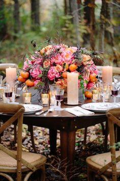 Flowers aren't the only thing spilling out of this wedding centerpiece—oranges also make an appearance, greeting the fall season in style.